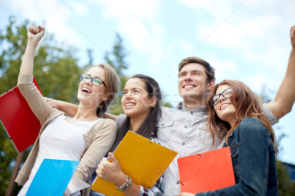 group of happy students showing triumph gesture Stock photo © dolgachov