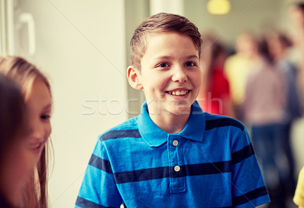 group of smiling school kids in corridor Stock photo © dolgachov