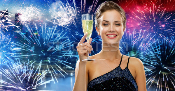 happy woman with glass of champagne over firework Stock photo © dolgachov