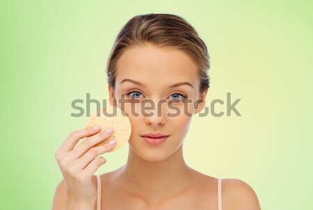 young woman cleaning face with exfoliating sponge Stock photo © dolgachov