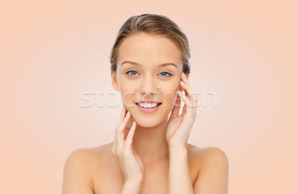 smiling young woman touching her face Stock photo © dolgachov