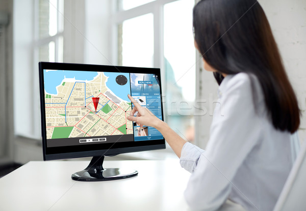 close up of woman with navigator map on computer Stock photo © dolgachov