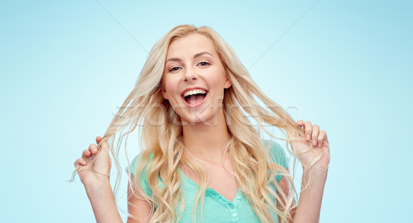 smiling young woman holding her strand of hair Stock photo © dolgachov