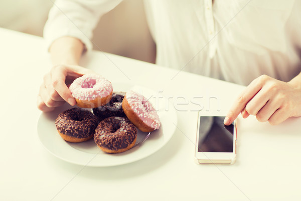 close up of hands with smart phone and donuts Stock photo © dolgachov