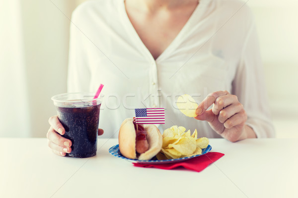 close up of woman eating chips, hot dog and cola Stock photo © dolgachov