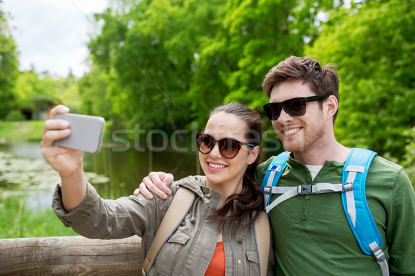 couple with backpacks taking selfie by smartphone Stock photo © dolgachov
