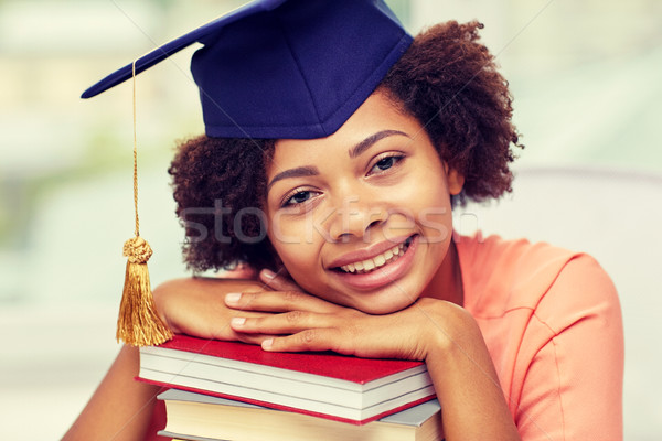 happy african bachelor girl with books at home Stock photo © dolgachov