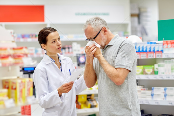 pharmacist and senior man with flu at pharmacy Stock photo © dolgachov