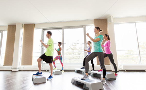 group of people exercising on steppers in gym Stock photo © dolgachov