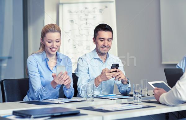 Stok fotoğraf: Gülen · iş · adamları · akıllı · telefonlar · ofis · teknoloji · iş · ekibi