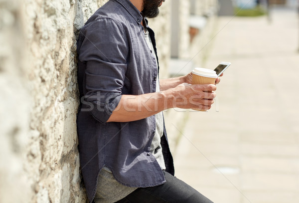 man with smartphone drinking coffee on city street Stock photo © dolgachov