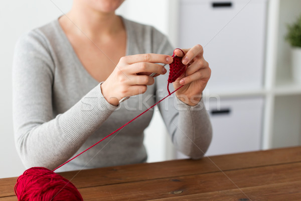 woman knitting with crochet hook and red yarn Stock photo © dolgachov