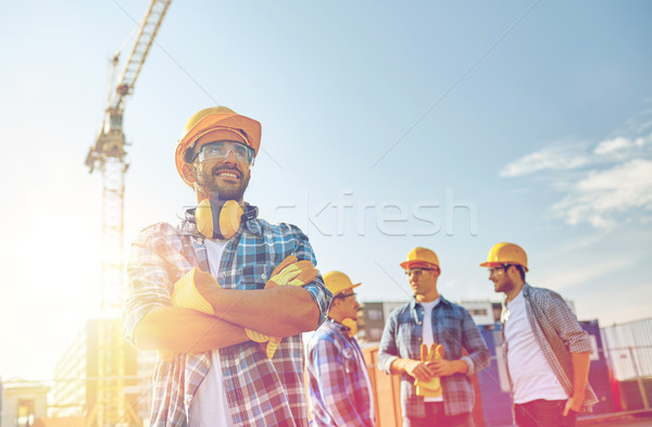 group of smiling builders in hardhats outdoors Stock photo © dolgachov