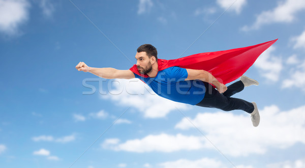 man in red superhero cape flying over blue sky Stock photo © dolgachov