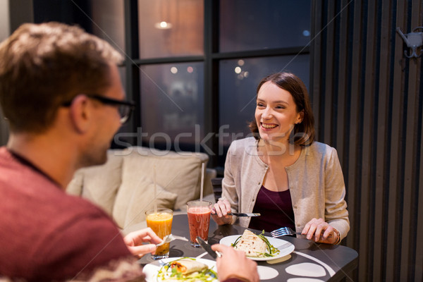 happy couple eating dinner at vegan restaurant Stock photo © dolgachov