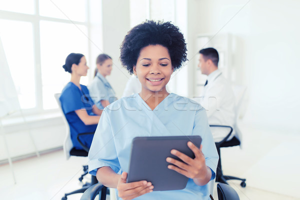 happy nurse with tablet pc over team at hospital Stock photo © dolgachov