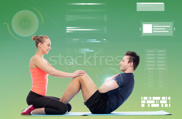 happy sportive man and woman doing sit-ups Stock photo © dolgachov