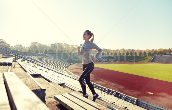 happy young woman running upstairs on stadium Stock photo © dolgachov