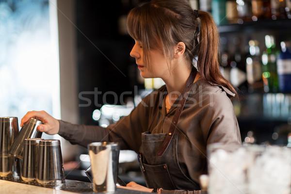 barmaid with shakers preparing cocktail at bar Stock photo © dolgachov
