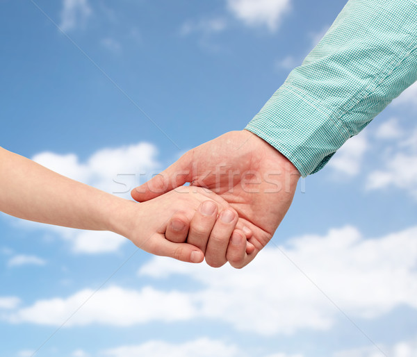 father and child holding hands over blue sky Stock photo © dolgachov
