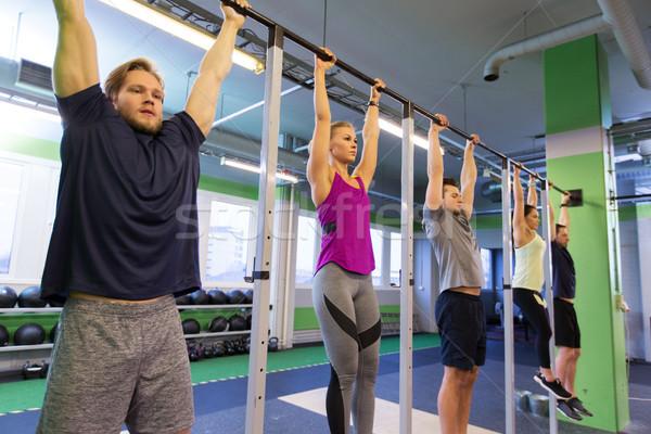 Groep mensen opknoping horizontaal bar gymnasium sport Stockfoto © dolgachov