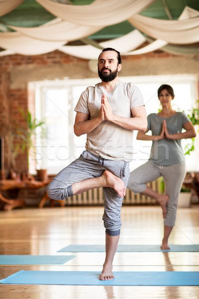 man and woman doing yoga tree pose at studio Stock photo © dolgachov