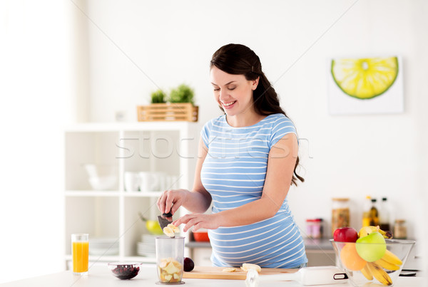 pregnant woman putting fruits to blender at home Stock photo © dolgachov
