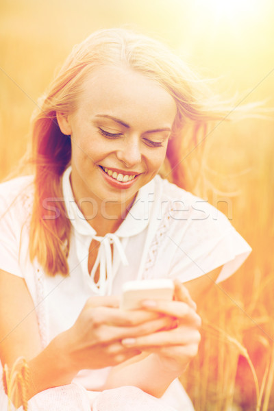 happy young woman with smartphone on cereal field Stock photo © dolgachov