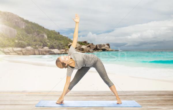 женщину йога треугольник создают пляж фитнес Сток-фото © dolgachov