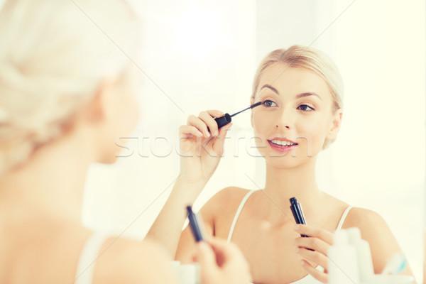 woman with mascara applying make up at bathroom Stock photo © dolgachov