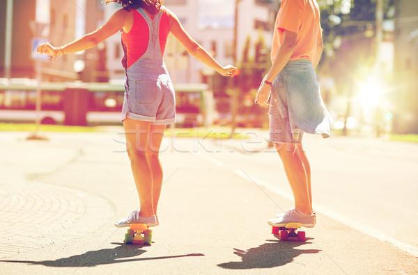teenage couple riding skateboards on city street Stock photo © dolgachov