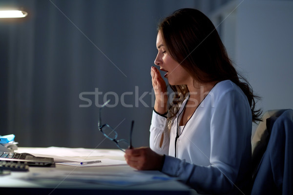 tired woman with glasses yawning at night office Stock photo © dolgachov