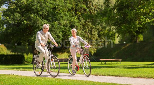 happy senior couple riding bicycles at summer park Stock photo © dolgachov