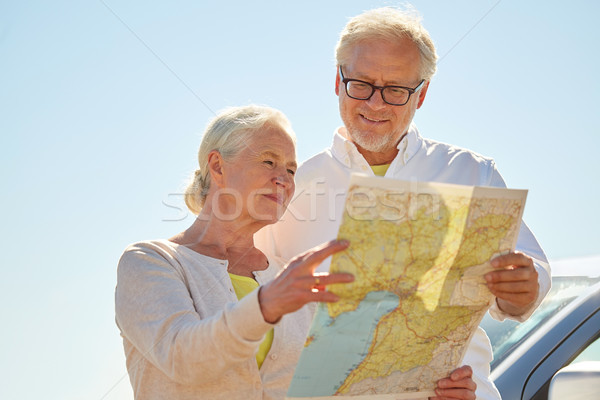 senior couple at car looking for location on map Stock photo © dolgachov