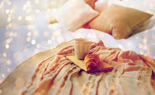 coffee cup and croissant on plaid in bed at home Stock photo © dolgachov