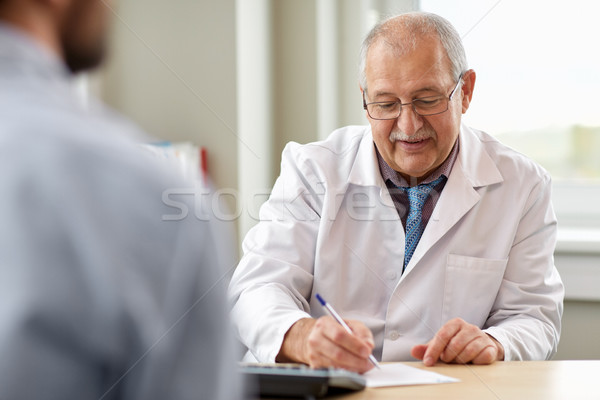 doctor writing prescription for patient at clinic Stock photo © dolgachov