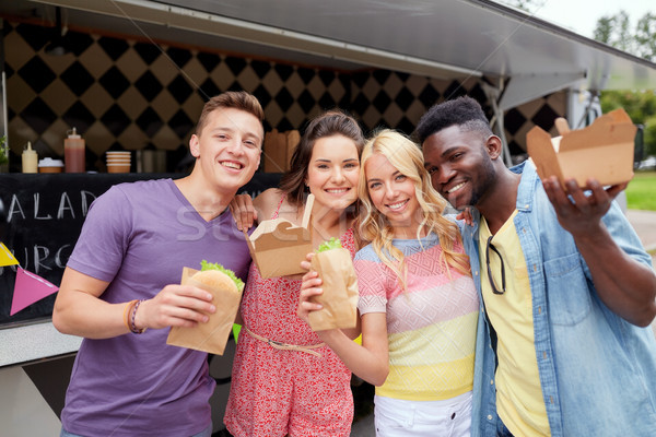 happy friends with wok and burger at food truck Stock photo © dolgachov