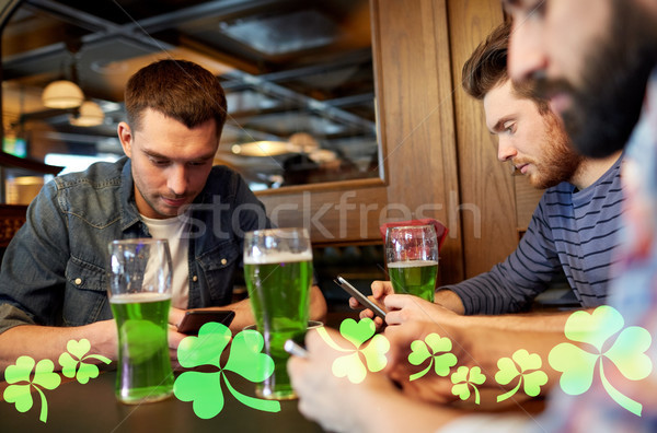 friends with smarphones and green beer at pub Stock photo © dolgachov