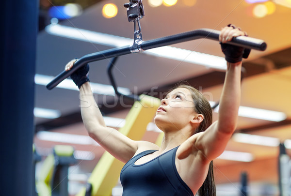 woman flexing arm muscles on cable machine in gym Stock photo © dolgachov