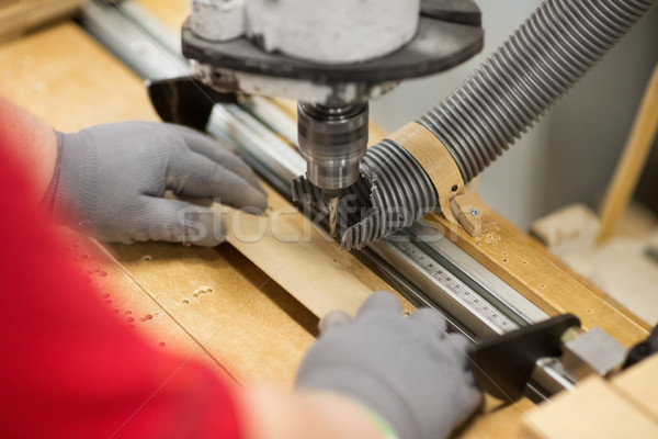 carpenter with drill press and board at workshop Stock photo © dolgachov