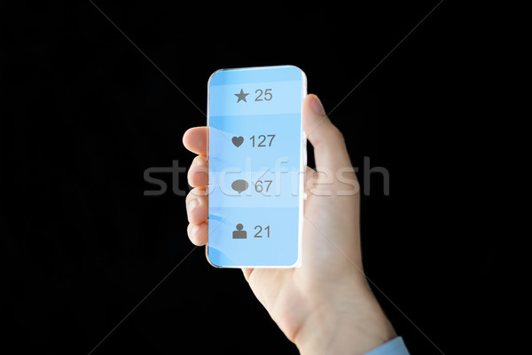 Stock photo: hand with social media icons on smartphone