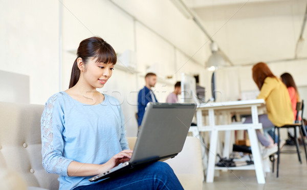 happy asian woman with laptop working at office Stock photo © dolgachov