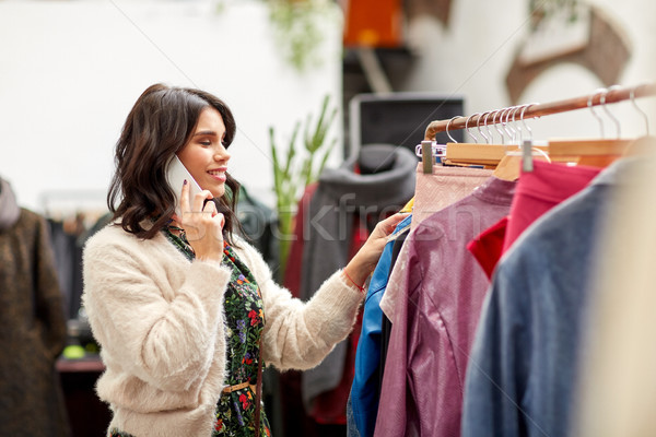 Stock photo: woman calling on smartphone at clothing store