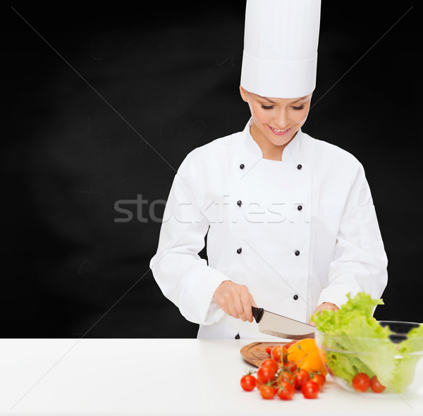 Stock photo: smiling female chef chopping vegetables