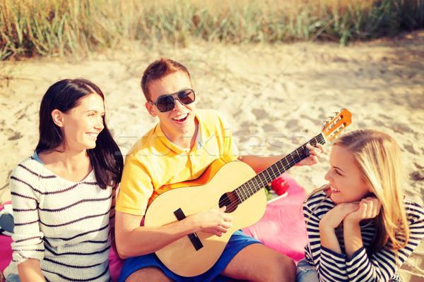 group of friends with guitar having fun on beach Stock photo © dolgachov