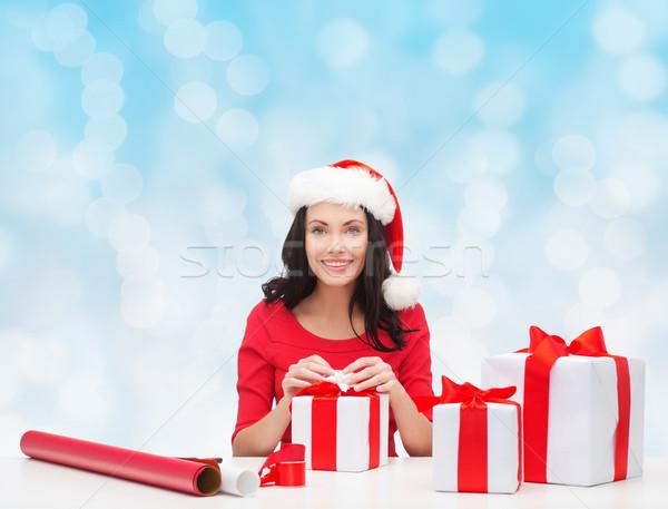 Mosolygó nő mikulás segítő sapkák csomagol ajándékok Stock fotó © dolgachov