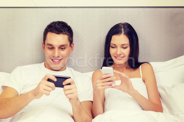 smiling couple in bed with smartphones Stock photo © dolgachov