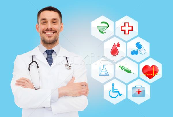 Sorridente médico do sexo masculino estetoscópio saúde profissão símbolos Foto stock © dolgachov