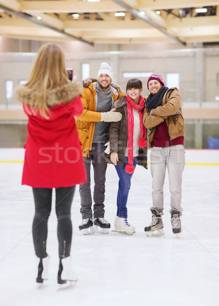 happy friends taking photo on skating rink Stock photo © dolgachov