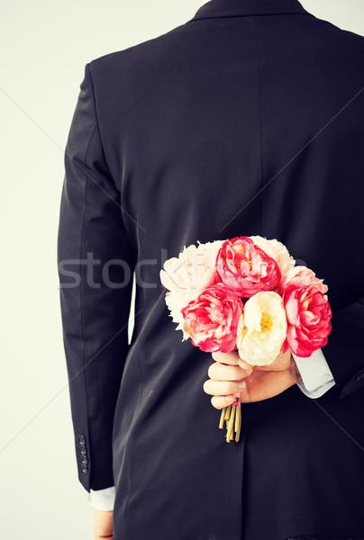 Férfi rejtőzködik virágcsokor virágok mögött hát Stock fotó © dolgachov